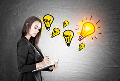 Businesswoman with a planner, many lightbulbs. Portrait of a beautiful young businesswoman wearing a black suit and holding a planner and a pen taking notes Stock Photos