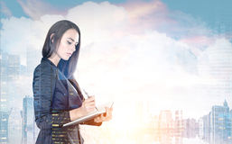 Businesswoman with a planner, morning city. Portrait of a beautiful young businesswoman wearing a black suit and holding a planner and a pen taking notes Stock Photography