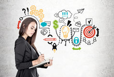 Businesswoman with a planner, startup scheme. Portrait of a beautiful young businesswoman wearing a black suit and holding a planner and a pen taking notes Royalty Free Stock Photo