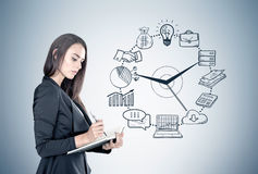 Businesswoman with a planner, time management. Portrait of a beautiful young businesswoman wearing a black suit and holding a planner and a pen taking notes Royalty Free Stock Photo