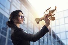Businesswoman play with a toy aircraft. Concept of company startup and business success. Businesswoman play with a wooden toy aircraft. Concept of company stock photo