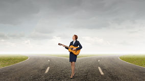 Businesswoman playing acoustic guitar Stock Photography
