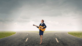 Businesswoman playing acoustic guitar Royalty Free Stock Photo