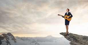 Businesswoman playing acoustic guitar Stock Image