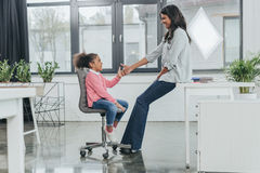 Businesswoman playing with daughter at workplace in business office. Side view of businesswoman playing with daughter at workplace in business office Royalty Free Stock Image