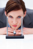 Businesswoman playing with kinetic balls stock image