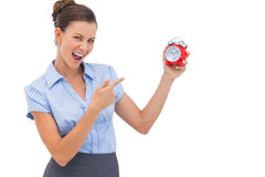 Businesswoman pointing at alarm clock Stock Image