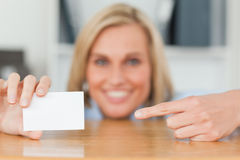 Businesswoman pointing at a card crouching Royalty Free Stock Photography