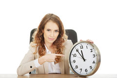 Businesswoman pointing on a clock by a desk. Royalty Free Stock Photos