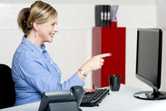 Businesswoman pointing at computer screen Royalty Free Stock Photos