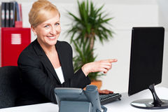 Businesswoman pointing at computer screen Stock Image
