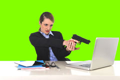 Businesswoman pointing gun to computer laptop sitting at office  green chroma key Royalty Free Stock Photography