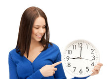 Businesswoman pointing her finger at wall clock Royalty Free Stock Images