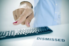Businesswoman pointing with her finger the way out. Closeup of a businesswoman sitting at her desk, with a document with the text dismissed on it, pointing with Royalty Free Stock Photo