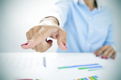 Businesswoman pointing with her finger the way out. Closeup of a businesswoman sitting at her desk, full of charts, pointing with her finger the way out Royalty Free Stock Photo