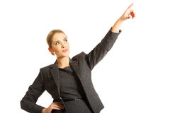 Businesswoman pointing high on copyspace Royalty Free Stock Photos