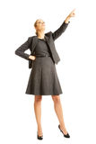 Businesswoman pointing high on copyspace Royalty Free Stock Image