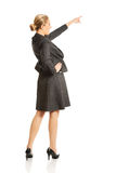 Businesswoman pointing high on copyspace Royalty Free Stock Photo