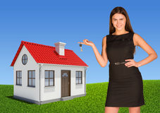 Businesswoman pointing at house, showing key Stock Images