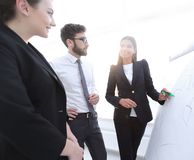 Businesswoman pointing marker to flipboard on presentation in office Stock Image