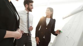 Businesswoman pointing marker to flipboard on presentation in office Royalty Free Stock Photos