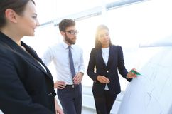 Businesswoman pointing marker to flipboard on presentation in office Stock Photography