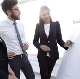 Businesswoman pointing marker to flipboard on presentation in office Stock Photo