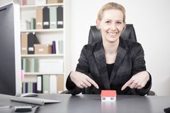 Businesswoman Pointing at Miniature House on Desk Royalty Free Stock Photography