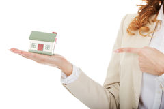 Businesswoman pointing on a model house. Royalty Free Stock Image