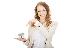 Businesswoman pointing on a model house. Stock Images