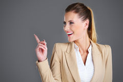 Businesswoman pointing over grey background Royalty Free Stock Image