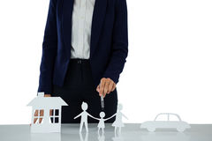 Businesswoman pointing on a paper cut out of family, car and house Stock Photo