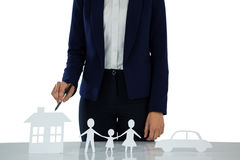 Businesswoman pointing on a paper cut out of family, car and house Stock Image