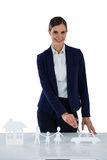 Businesswoman pointing on a paper cut out of family, car and house Royalty Free Stock Image