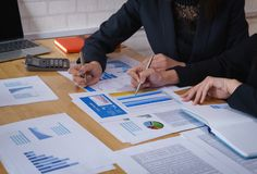 Businesswoman pointing pen on business document at meeting room.Discussion and analysis data charts and graphs showing the results stock photo