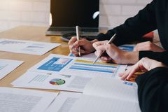 Businesswoman pointing pen on business document at meeting room.Discussion and analysis data charts and graphs showing the results stock image