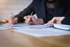Businesswoman pointing pen on business document at meeting room.Discussion and analysis data charts and graphs showing the results stock images