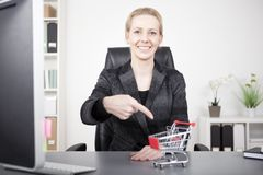 Businesswoman Pointing at Small Cart on her Desk Stock Images