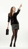 Businesswoman pointing at something. Young attractive businesswoman pointing at something holding bag; neutral background royalty free stock images