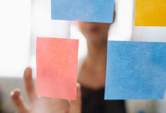 Businesswoman pointing at sticky note on glass wall. Hand of businesswoman pointing at a sticky note on a glass wall while standing in office. Focus on adhesive Stock Photo