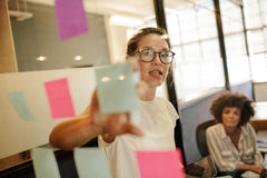 Businesswoman pointing at sticky note to colleague. Business women pointing at sticky note to female colleague on glass wall in office. Business people working Stock Images