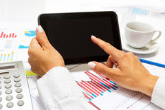 Businesswoman pointing on tablet, inside bright office. Royalty Free Stock Image
