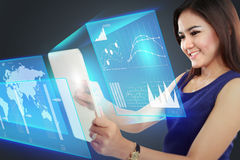 Businesswoman pointing to a graph on transparent touchscreen Stock Photography