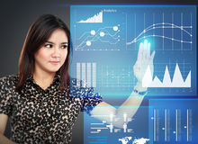 Businesswoman pointing to a graph on transparent touchscreen Stock Photo