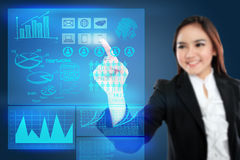 Businesswoman pointing to a graph on transparent touchscreen Royalty Free Stock Image