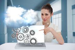Businesswoman pointing to her laptop showing cogs and wheels Royalty Free Stock Photos