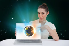 Businesswoman pointing to her laptop showing earth graphic Stock Photography