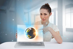 Businesswoman pointing to her laptop showing earth graphic Stock Photos