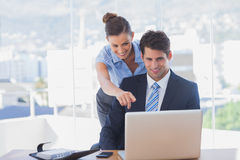 Businesswoman pointing to the laptop and smiling Stock Photos