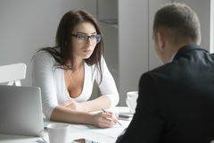 Businesswoman pointing to a mistake in a paper. Young boss businesswoman talking to employee, pointing to a mistake in a paper, incorrectly done task by a men or Royalty Free Stock Photography